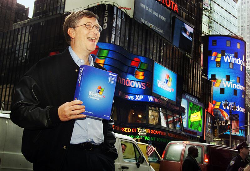 Bill Gates a segurar caixa do Windows XP em frente à Bolsa de Valores NASDAQ
